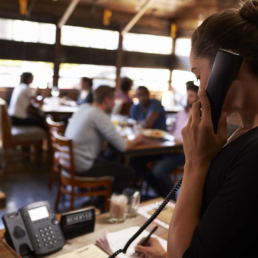 קופאית לוקחת הזמנה מהטלפון בגלל שאין למסעדה שבה היא עובדת אפליקציה לעסק