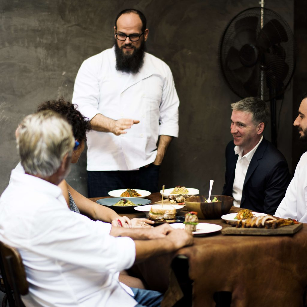 שף מסביר את בחירת המרכיבים במנה ללקוחות במסעדה.